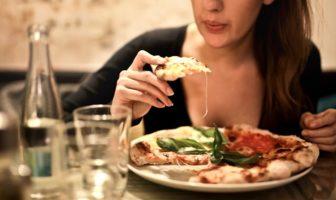 Жінка їсть піцу